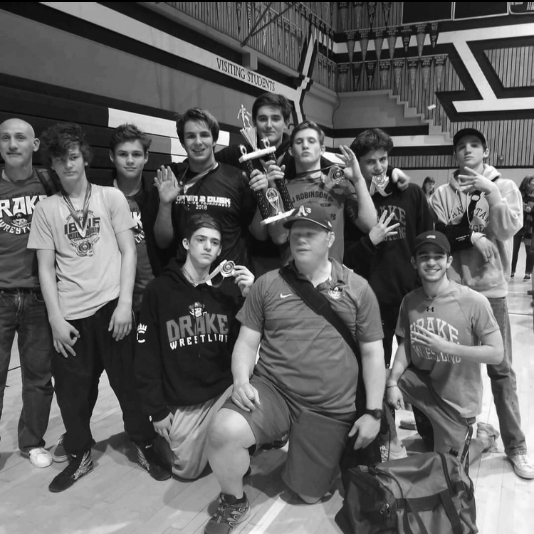 The wrestling team poses with their first ever trophy.
