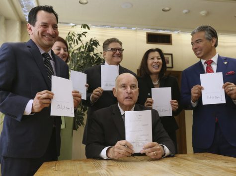 Governor Brown holds up a copy of the bill, surrounded by (left to right) Assembly Speaker Anthony Rendon (D-Los Angeles), Senate President pro Tempore Toni Atkins (D-San Diego), state Senator Bob Hertzberg (D-Van Nuys), California Supreme Court Chief Justice Tani Cantil-Sakauye, and Assemblyman Rob Bonta (D-Alameda)