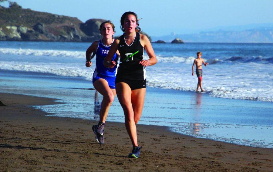 On September 12 at Stinson Beach, Junior Ava Podboy keeps her lead ahead of a Tam runner.
