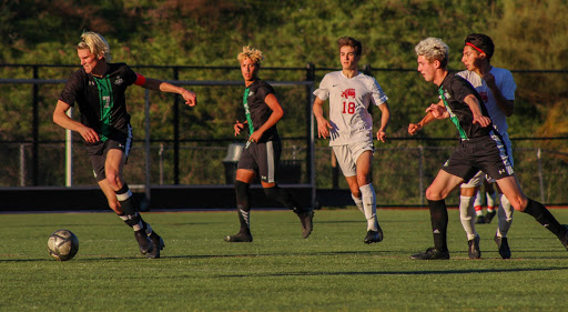Senior Logan Smith leads the pack with the ball, juniors Sage Urbaez and Daelan Boutwell follow closely behind.