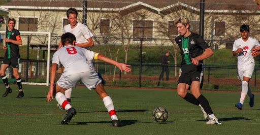 Sophomore George Dick maintains ball control while surrounded by San Rafael players.