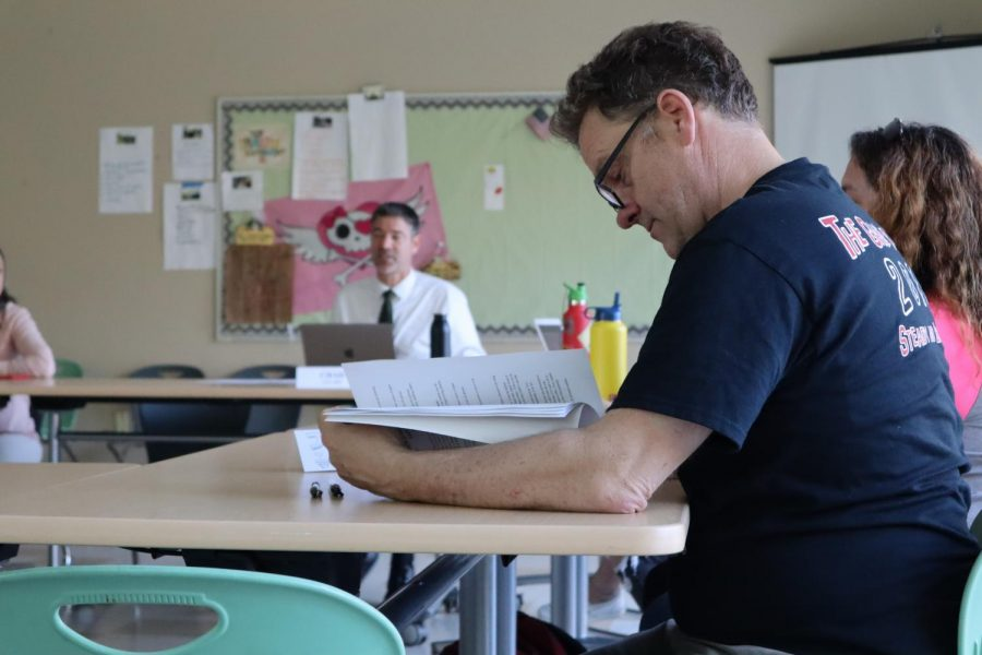 Teacher Jasper Thelin reads the school rules and safety codes packet, which was being passed around the room for approval.