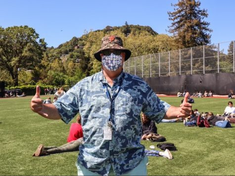Campus supervisor Rich Blasewitz throws up two shakas for the camera on the baseball field during lunch.