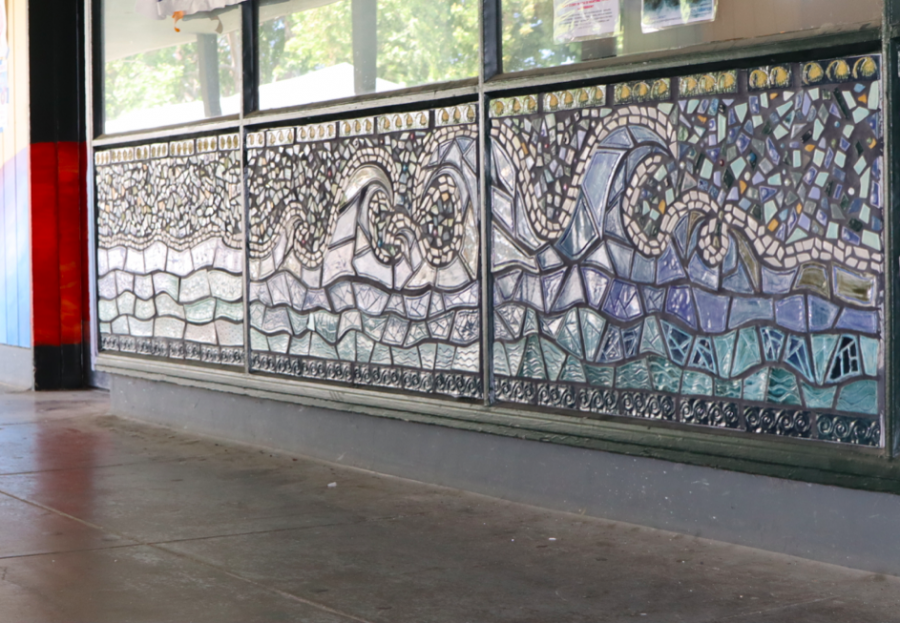 The three completed panels display an array of blue waves across the outside of the Wellness Center