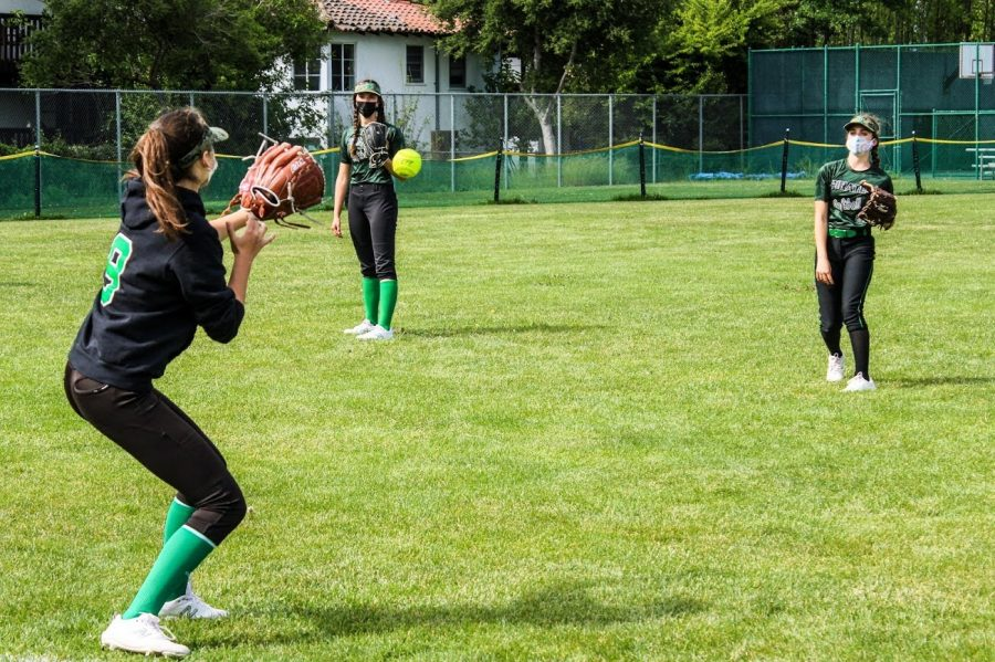Sofia Barker throws a softball to her teammates while Jasmin Desruisseau awaits her turn during passing drills.