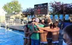 AWHS varsity boys embrace in a group hug following their win.