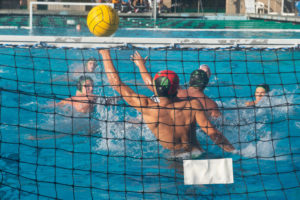 AWHS sophomore, and boys varsity goalie, Haakon Lacy, leaps out of the water to stop a shot from the opposing team.