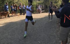 Junior Barret Acker lunging towards the finish line, with fans cheering him on.