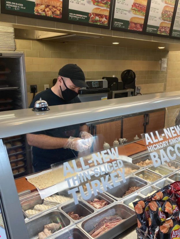 Ramy Iskander, manager of Subway's location in the Red Hill Shopping Complex, making a sandwich for a customer.