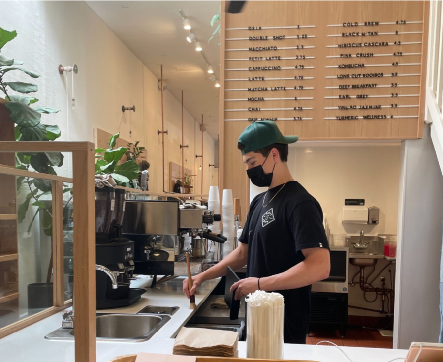 Dominic+Macaulay%2C+a+barista+in+the+cafe+located+in+the+back+of+Longway%2C+cleans+up+the+cafe+for+the+end+of+the+day.