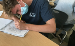 Sam Sobieraj studying and wearing a mask in an AWHS classroom.