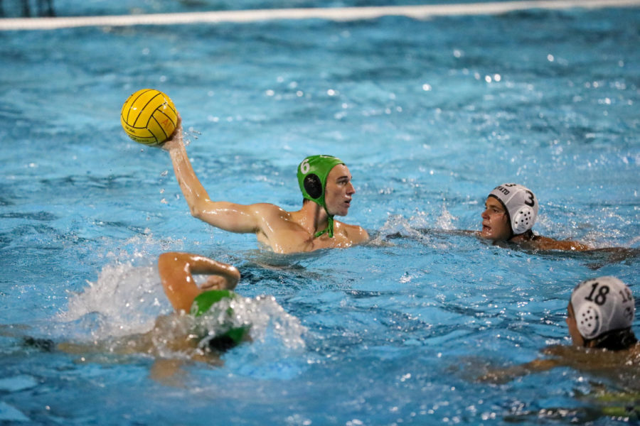 Senior Cole Wooster holds the ball out of the water while looking to pass it to a teammate.