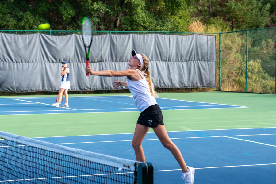 AWHS varsity girls tennis player, Sara Rice returns a hit, scoring a point in her doubles match against Marin Catholic.